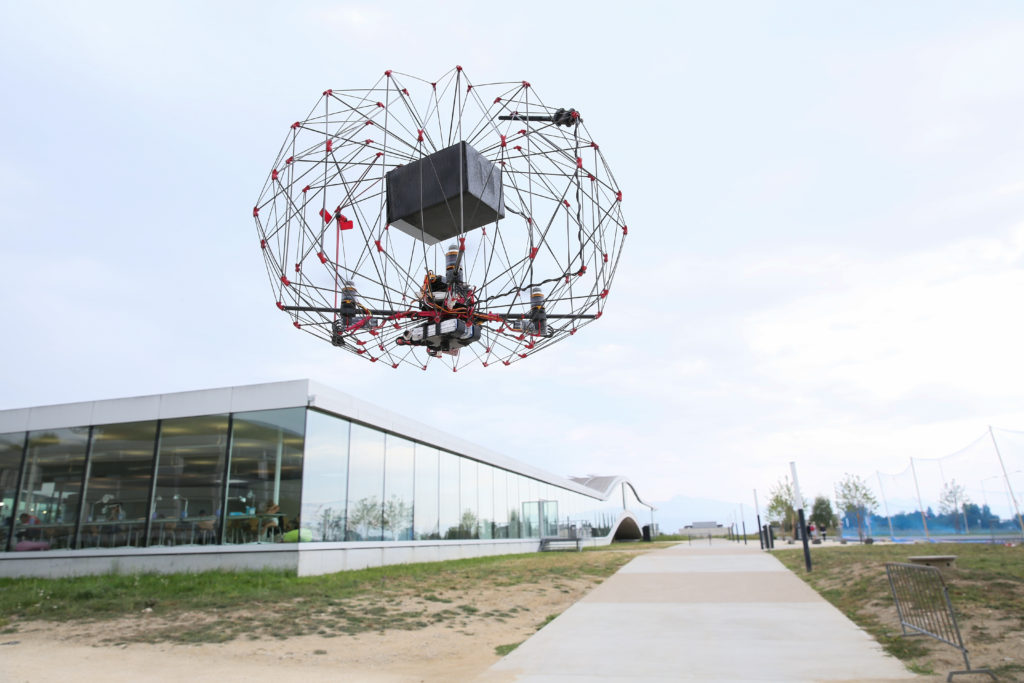 Picture of a flying drone with an exterior structure that protects it and a box inside that allows it to carry things