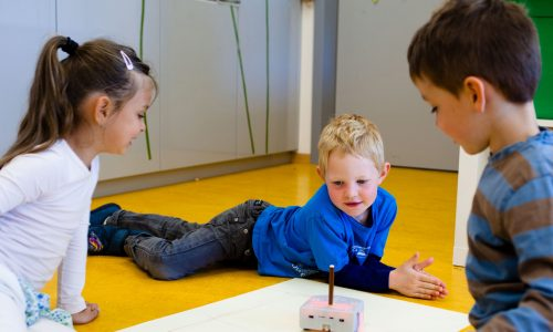 3 kids interact with the Thymio robot